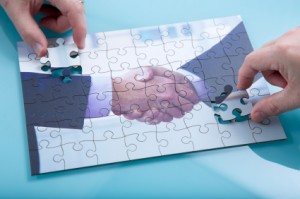 A jigsaw of a handshake being completed ny two hands.